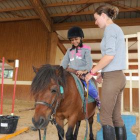 monitrice avec élève à cheval